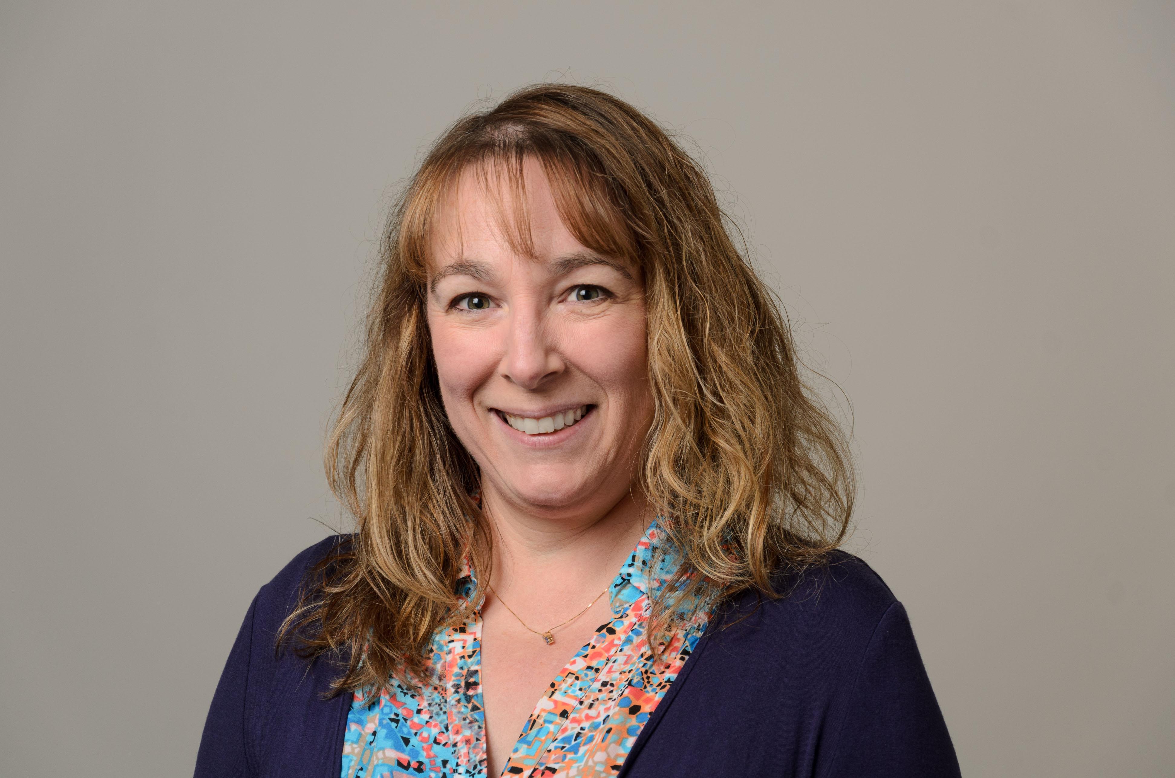 Headshot of Valerie Brangan. Teal patterned shirt, purple sweater.