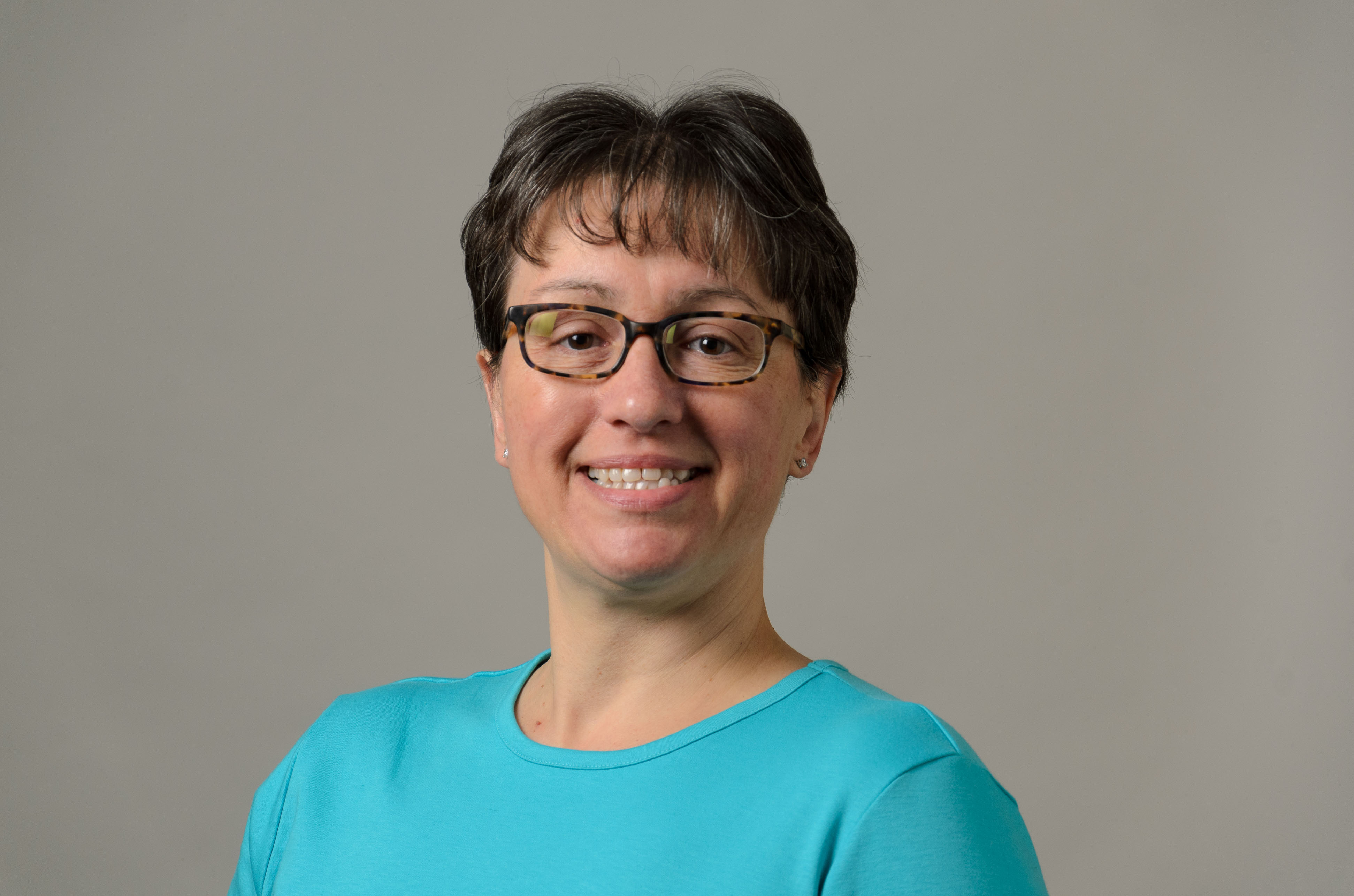 Headshot of Cheryl Lebeau Radzvilowicz. Teal shirt and glasses.