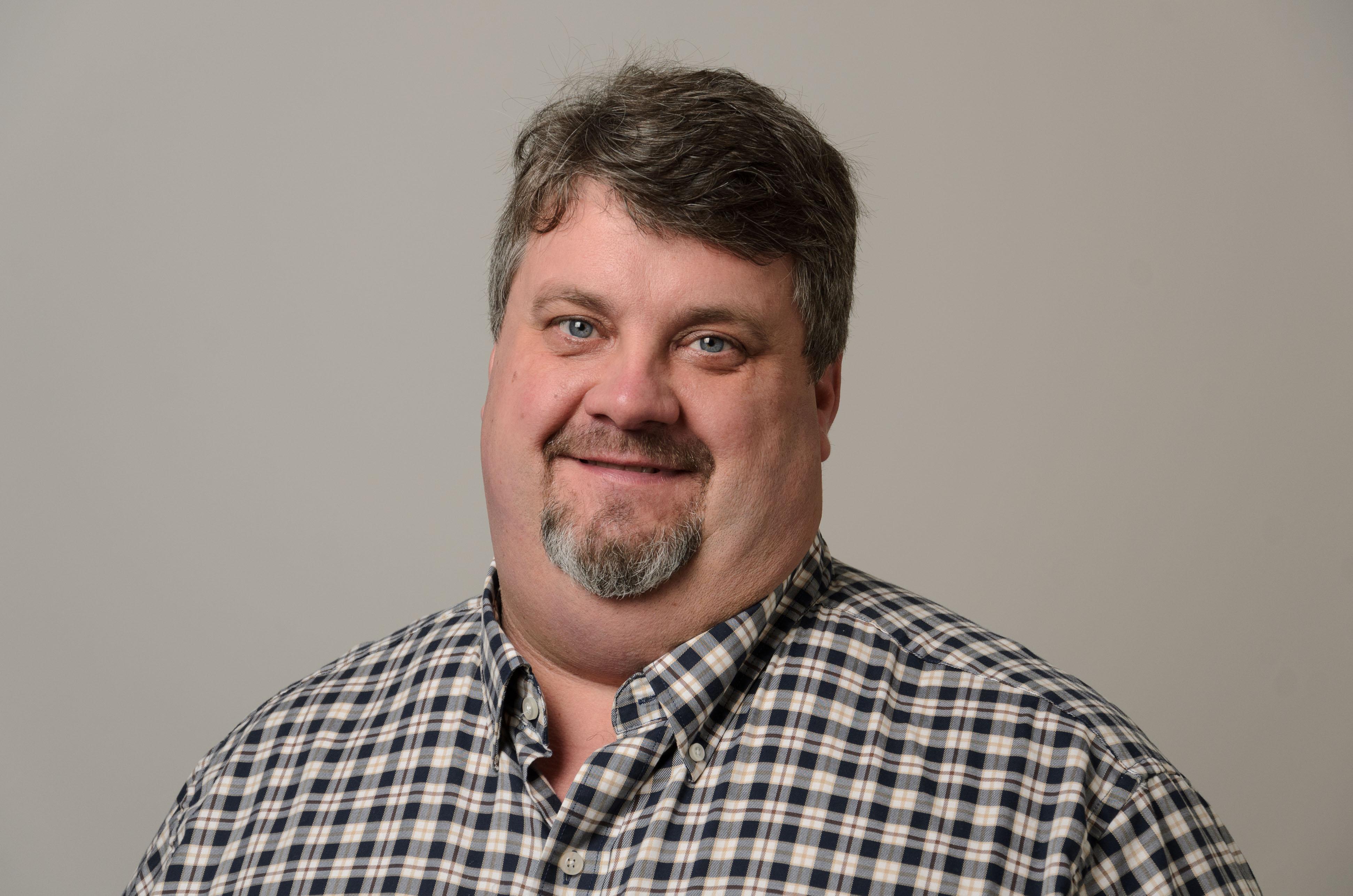 Headshot of Denis Shannon, plaid shirt
