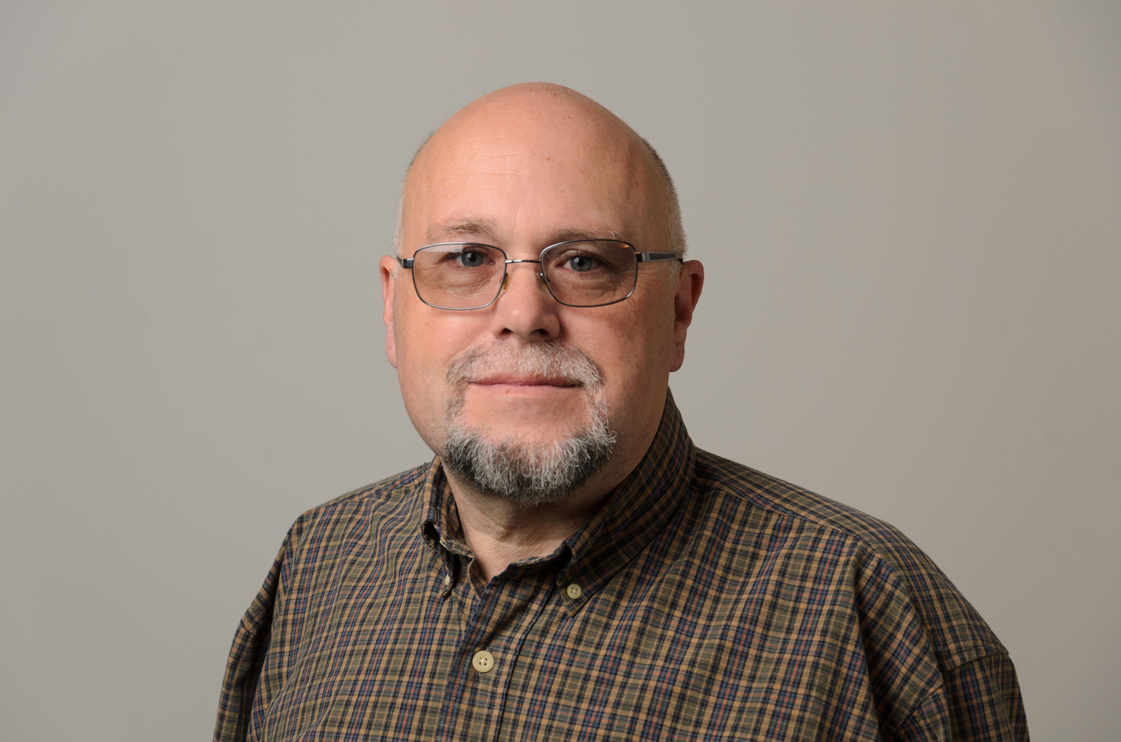 Headshot of David Judd. Plaid Shirt, Glasses.