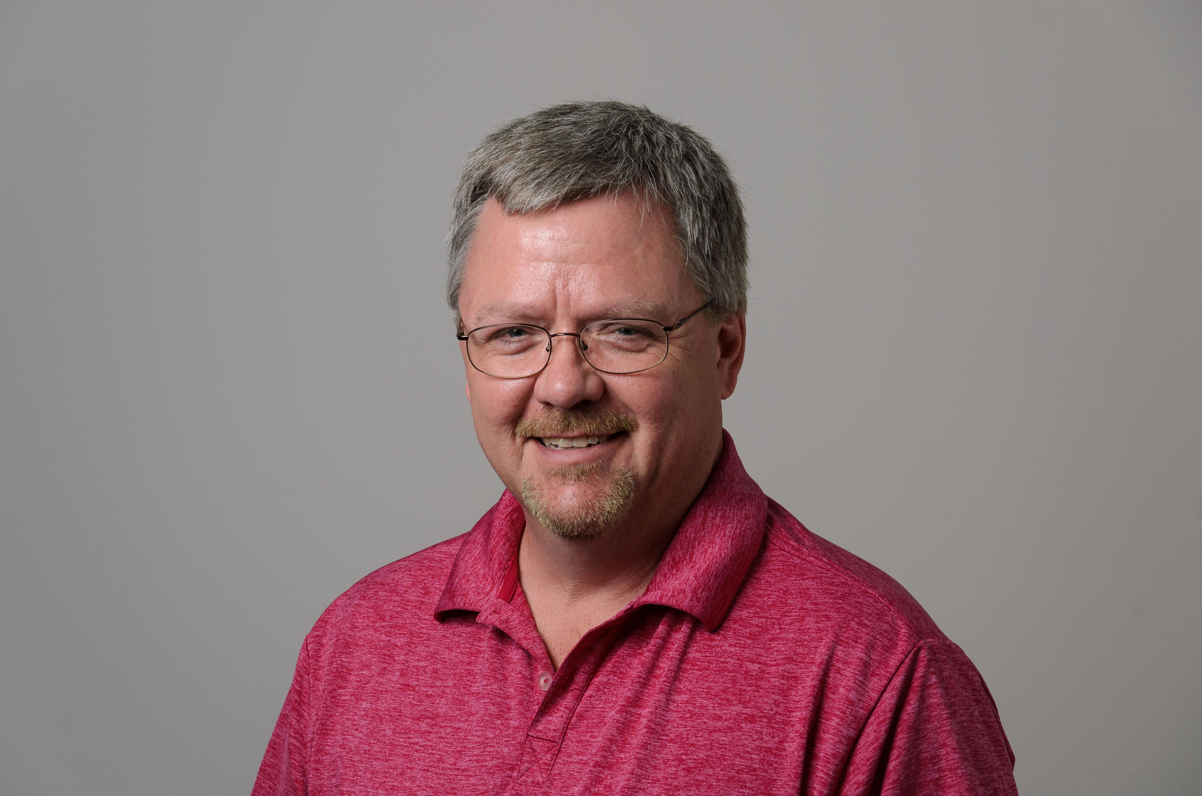 Headshot of William Field. Red Shirt.