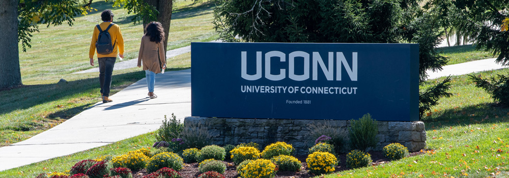 UConn gateway sign with students walking